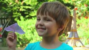 Junge, der mit einem Papierflugzeug spielt stock footage