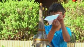 Junge, der mit einem Papierflugzeug spielt stock video