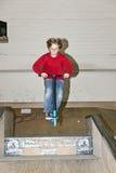 Junge, der mit einem Roller Bord geht Stockfotos