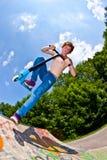 Junge, der mit einem Roller Bord geht Lizenzfreie Stockbilder