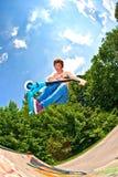 Junge, der mit einem Roller Bord geht Lizenzfreie Stockfotografie