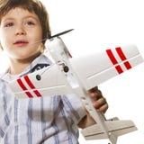 Junge, der mit einem Spielzeugflugzeug spielt Lizenzfreie Stockfotos