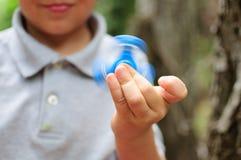 Junge, der mit einem Tri Unruhe-Handspinner spielt Stockbild