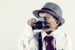 Junge, der mit einer alten Kamera spielt, um Fotograf zu sein Lizenzfreie Stockfotos