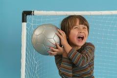 Junge, der mit einer socker Kugel spielt Stockbild