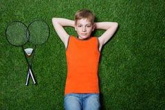 Junge, der mit Federballschläger auf grünem Gras liegt Stockbilder
