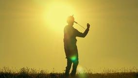 Junge, der mit Flugzeugmodell gegen orange Sonnenunterganghintergrund spielt