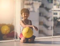 Junge, der mit Fu?ball auf dem Boden sitzt lizenzfreie stockbilder
