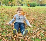 Junge, der mit gefallenen Blättern spielt stockbild