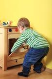 Junge, der mit hölzernem Ofen im Kindergarten spielt lizenzfreie stockbilder