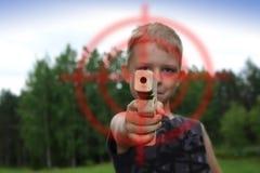 Junge, der mit hölzernem Spielzeuggewehr zeigt Lizenzfreies Stockfoto