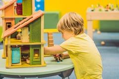 Junge, der mit Holzhaus im Kindergarten spielt stockbild