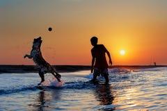 Junge, der mit Hund auf dem Strand spielt Stockbild