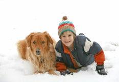 Junge, der mit Hund im Schnee spielt Lizenzfreie Stockfotos