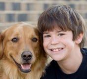 Junge, der mit Hund lächelt Stockbild