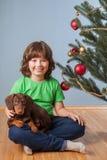 Junge, der mit Hund nahe dem Weihnachtstannenbaum spielt Lizenzfreie Stockfotos