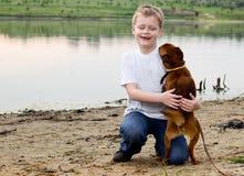 Junge, der mit Hund spielt. Stockfotografie
