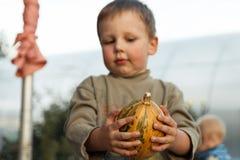 Junge, der mit Kürbis in den Händen steht lizenzfreie stockfotos