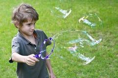 Junge, der mit Luftblasen spielt Lizenzfreie Stockbilder
