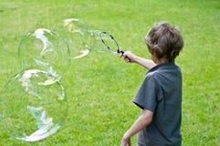 Junge, der mit Luftblasen spielt Stockfotografie