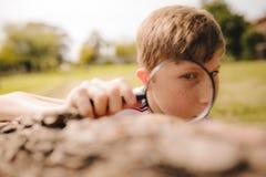 Junge, der mit Lupe erforscht lizenzfreie stockbilder