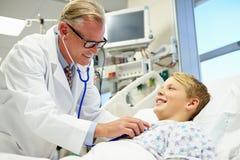 Junge, der mit männlichem Doktor In Emergency Room spricht Stockbild