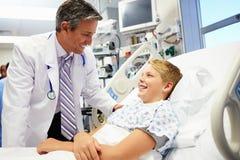 Junge, der mit männlichem Doktor In Emergency Room spricht Lizenzfreie Stockfotos