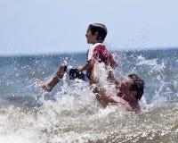 Junge, der mit Opa in der großen zusammenstoßenden Welle spielt Stockfotografie