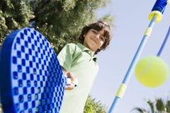 Junge, der mit Paddel und Ball spielt stockfoto