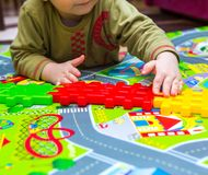 Junge, der mit Plastikblöcken im Haus spielt Stockfoto