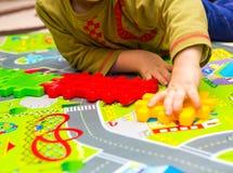 Junge, der mit Plastikblöcken im Haus spielt Stockbild