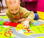 Junge, der mit Plastikblöcken im Haus spielt Lizenzfreie Stockfotos