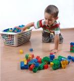 Junge, der mit Plastikblöcken spielt Stockbild