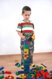 Junge, der mit Plastikblöcken spielt Stockfotografie