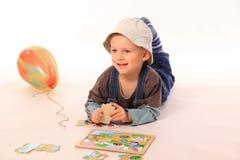 Junge, der mit Puzzlespiel spielt Lizenzfreie Stockfotos