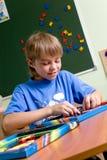 Junge, der mit Puzzlespielen spielt Stockbilder