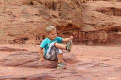 Junge, der mit Sand in einer Wüste spielt Lizenzfreies Stockbild