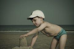 Junge, der mit Sand spielt Lizenzfreie Stockbilder