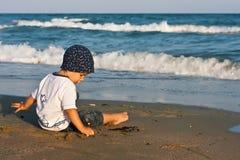 Junge, der mit Sand spielt Stockbild