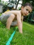 Junge, der mit Schlauch spielt Stockfotos