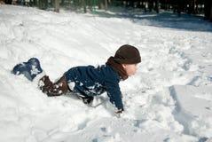 Junge, der mit Schnee spielt Stockfotos