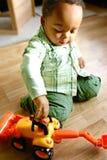 Junge, der mit seinem LKW spielt Stockbild