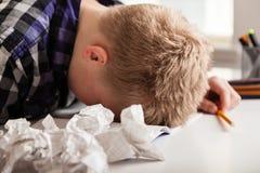 Junge, der mit seiner Hausarbeit kämpft Lizenzfreies Stockfoto