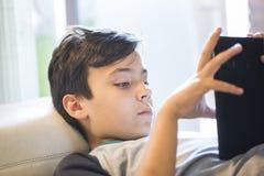 Junge, der mit seiner Tablette spielt Lizenzfreie Stockfotos