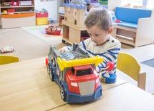 Junge, der mit Spielwaren im Kindergarten spielt lizenzfreies stockbild