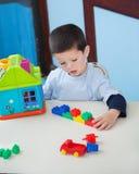 Junge, der mit Spielwaren am Schreibtisch in der Vorschule spielt Lizenzfreies Stockbild