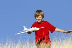 Junge, der mit Spielzeug-Segelflugzeug-Flugzeug spielt Stockfotos