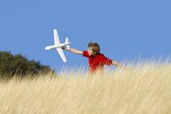 Junge, der mit Spielzeug-Segelflugzeug-Flugzeug spielt Lizenzfreies Stockfoto