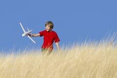 Junge, der mit Spielzeug-Segelflugzeug-Flugzeug spielt Stockbilder
