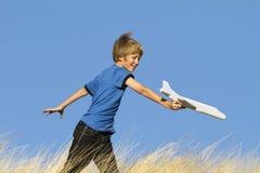 Junge, der mit Spielzeug-Segelflugzeug-Flugzeug spielt Lizenzfreie Stockfotografie